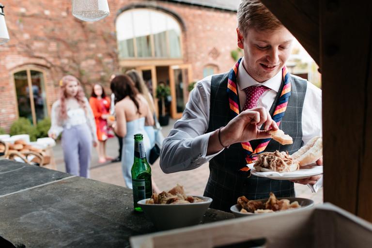 groom enjoying hog roast cob