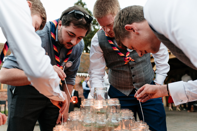 groomsmen lighting the candle camp fire