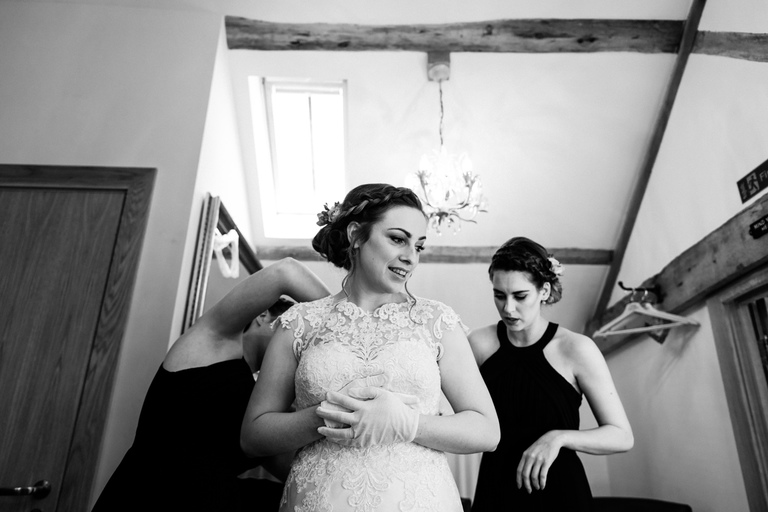 bride being zipped into her dress
