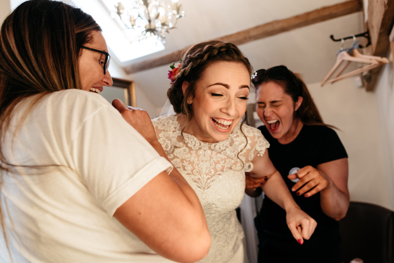 bride laughing with hairdresser