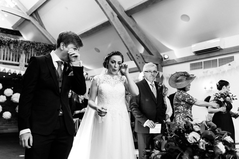 bride and groom wiping away tears