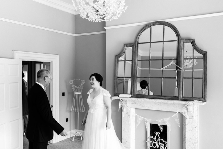father of the bride sees his daughter in her dress