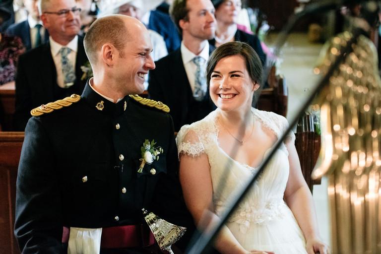 happy couple exchange smiles in church