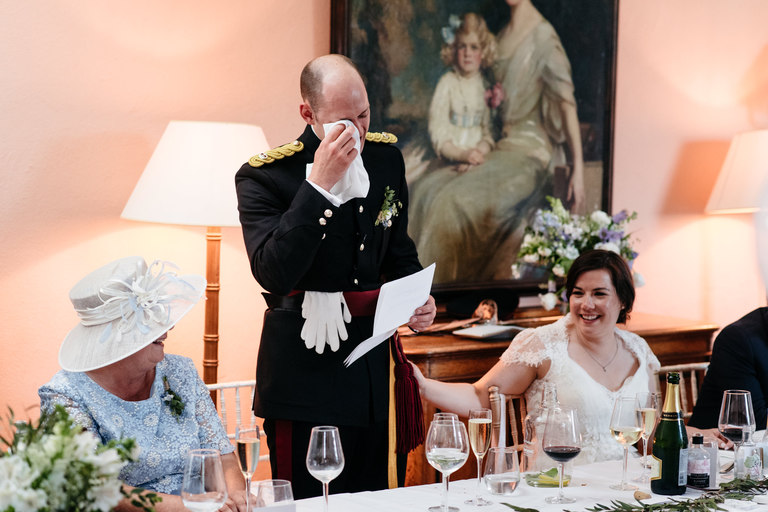 groom wipes away a tear during his speech
