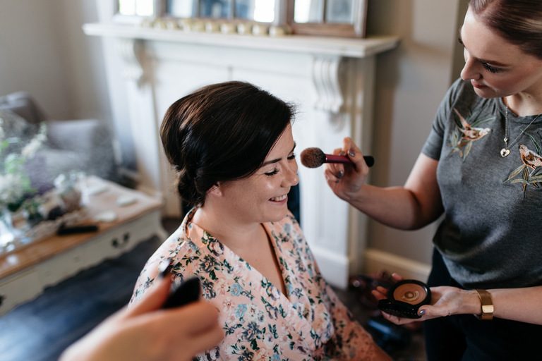 smiling bride having makeup applied