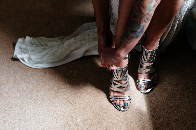 tattooed bride putting on her shoes