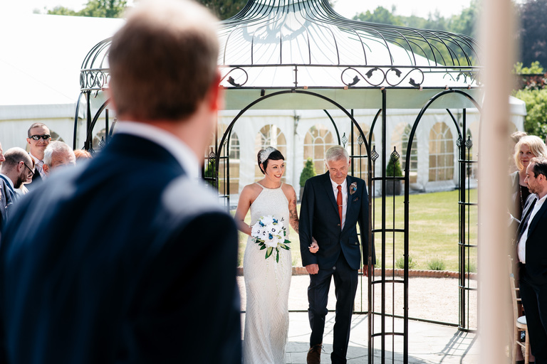 bride walking with her father at beeston walled gardens