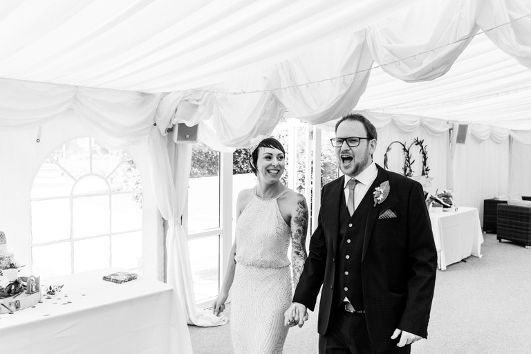 newlyweds walking into the marquee at beeston fields