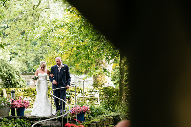 bride walking down stairs with her father garden wedding