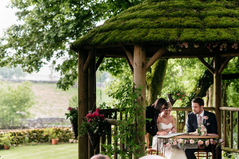 signing the register outdoors with countryside in the background