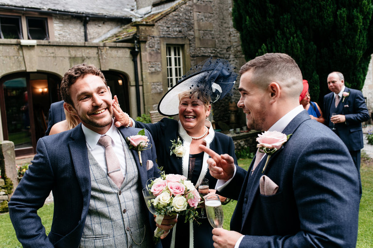mother of the groom wiping her son's cheek