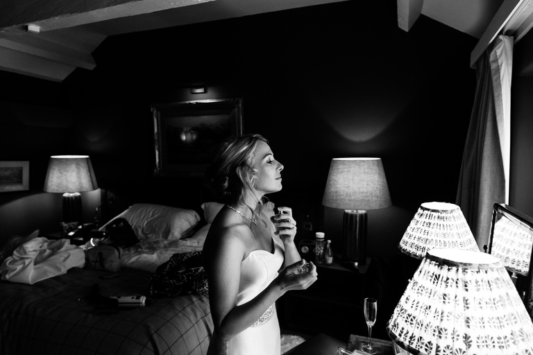 bride spraying perfume in the hotel room