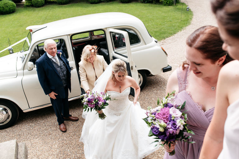 bride arriving at hampton court house in a white London taxi