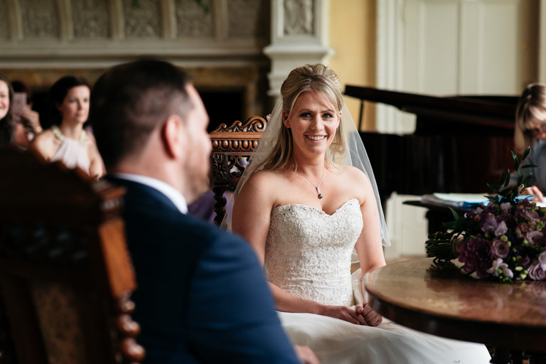 smiling, happy bride sat down looking at her husband