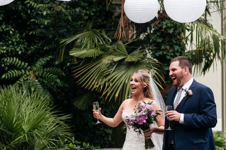 newlyweds walking into their drinks reception amidst the ferns