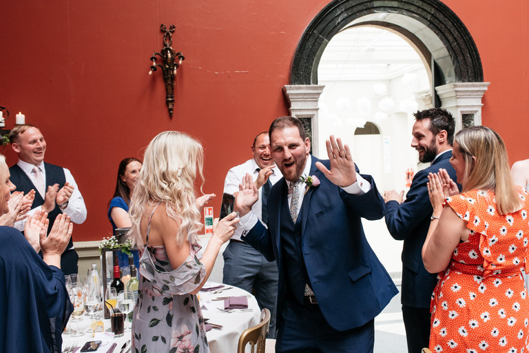 groom giving guests high fives as he walks into the wedding breakfast