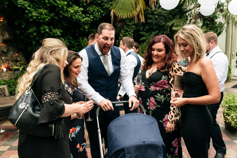 groom pushing a pram surrounded by women