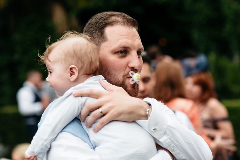groom sucking a dummy holding his son