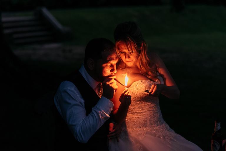 bride and groom sharing a cigar at night