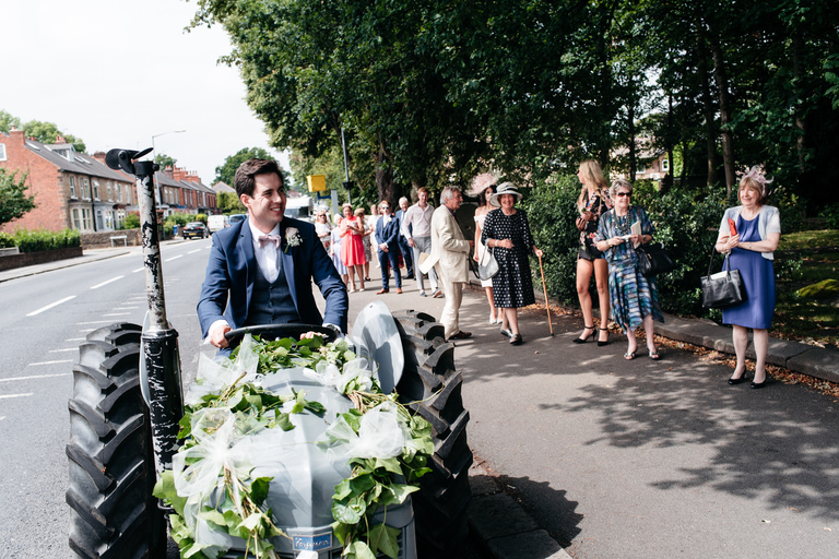 groom arriving at the church on a tractor