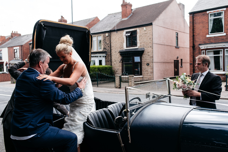 bride's dad helping her out of the wedding car