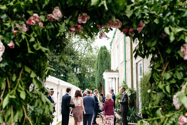 view of guests through a flower arch