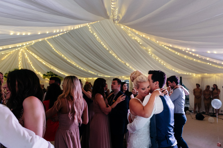 couple dancing with guests on the dance floor