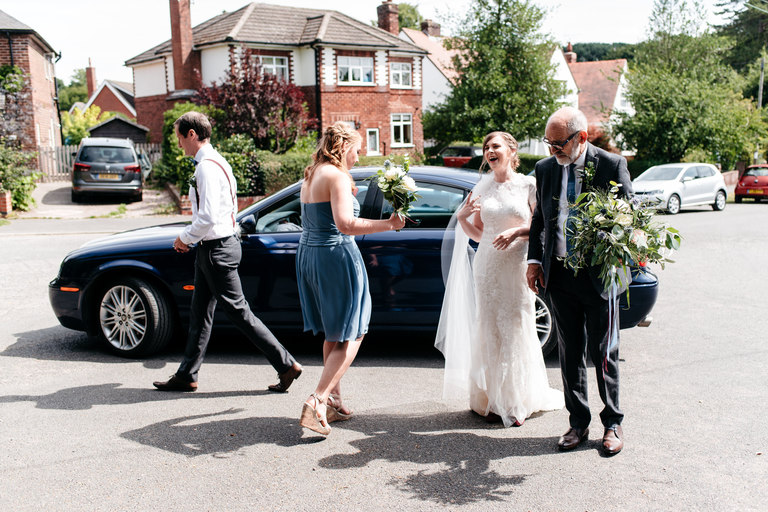 bride getting out of wedding car on a sunny day
