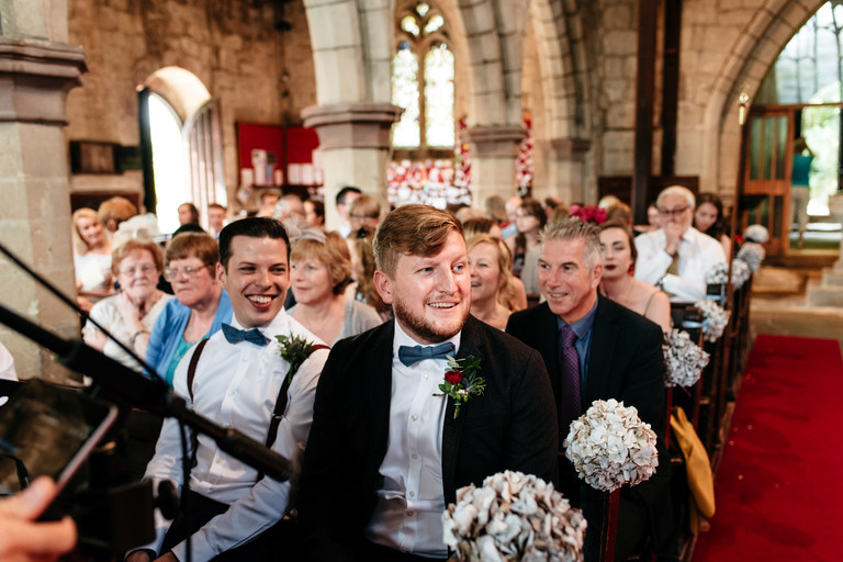 excited groom waiting in church