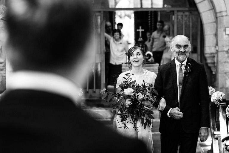 happy bride walking down the aisle with her father