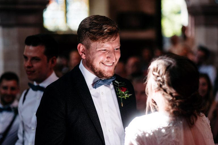 happy groom beaming at his new wife