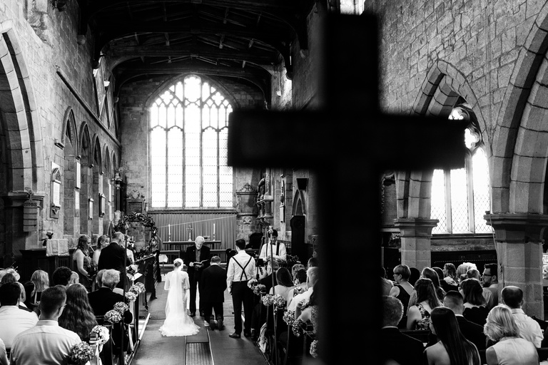 just married couple kneeling in church in front of the cross