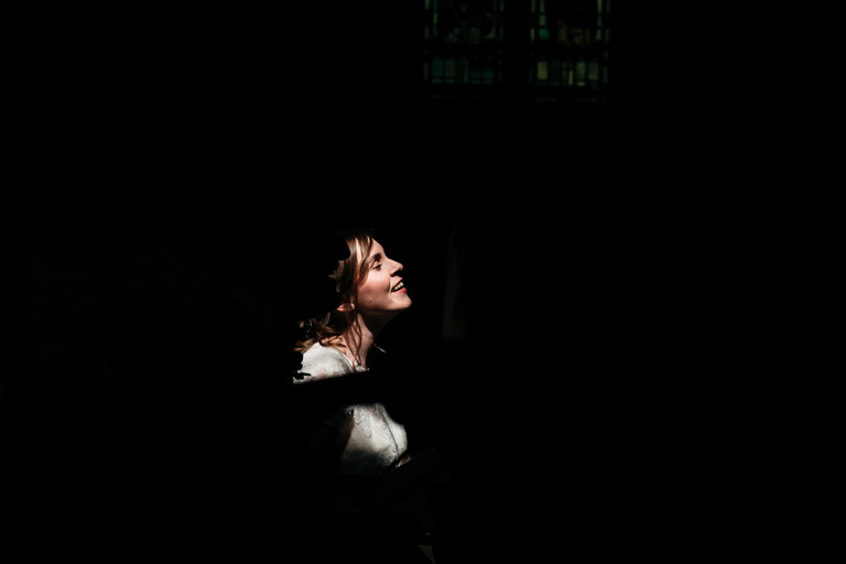 bride's face highlighted by sunlight in church