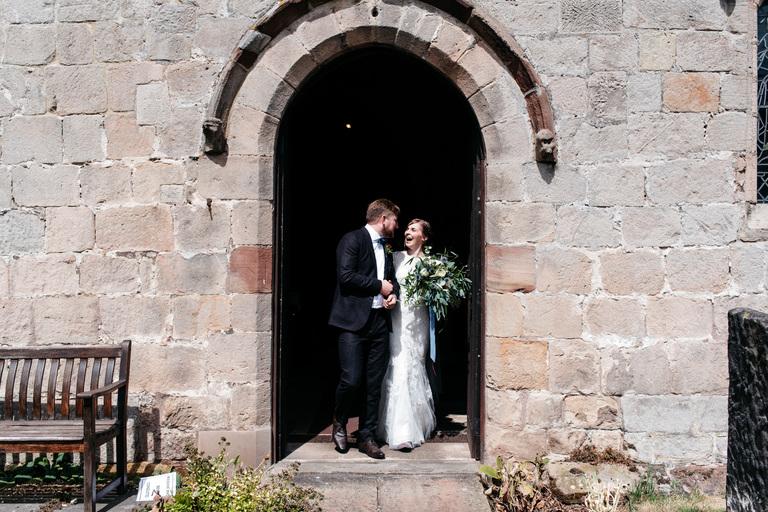 newlyweds in the doorway of the church
