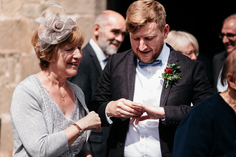 groom showing his wedding ring to his mother