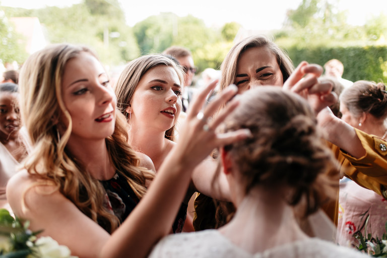 friends picking confetti out of the bride's hair