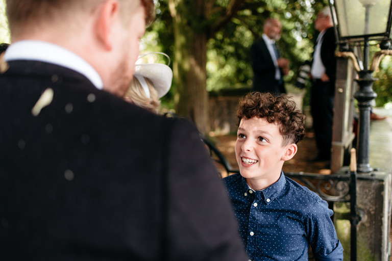 young boy smiling up at the groom