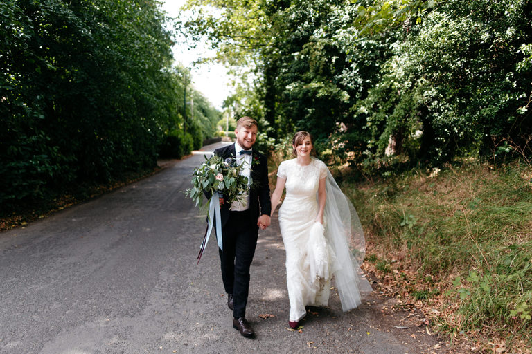 newlyweds walking down a sunny country lane together