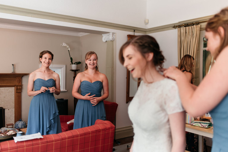 smiling bridesmaids looking at the bride in her dress