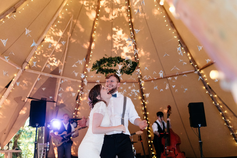 bride and groom laughing first dance teepee