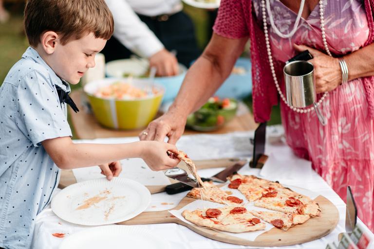little boy taking a slice of pizza