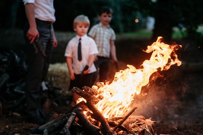two boys admiring a roaring bonfire