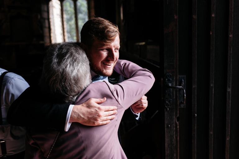 groom hugging guests at church