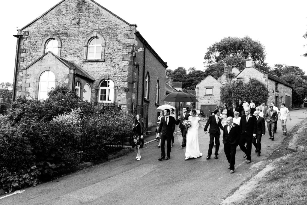wedding party walking down the hill in hartington village