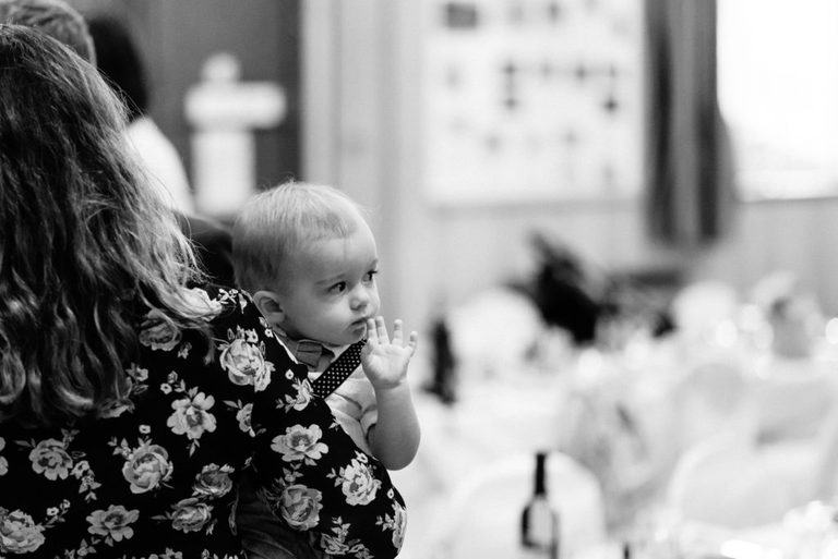 black and white photograph of a baby at a wedding