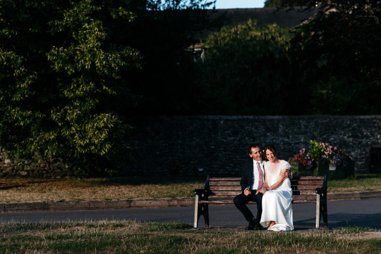 golden hour wedding portrait on the village bench