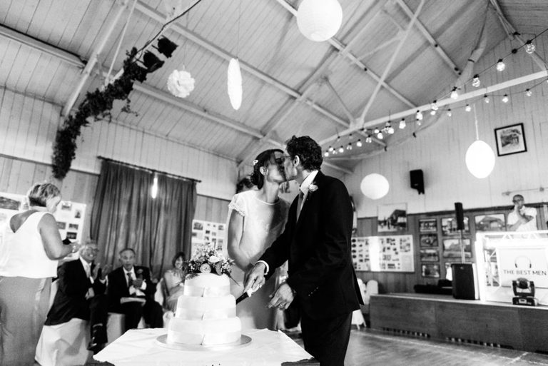 sharing a kiss whilst cutting the cake