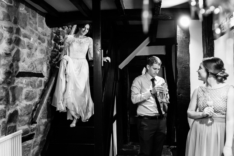 bride in her dress coming downstairs