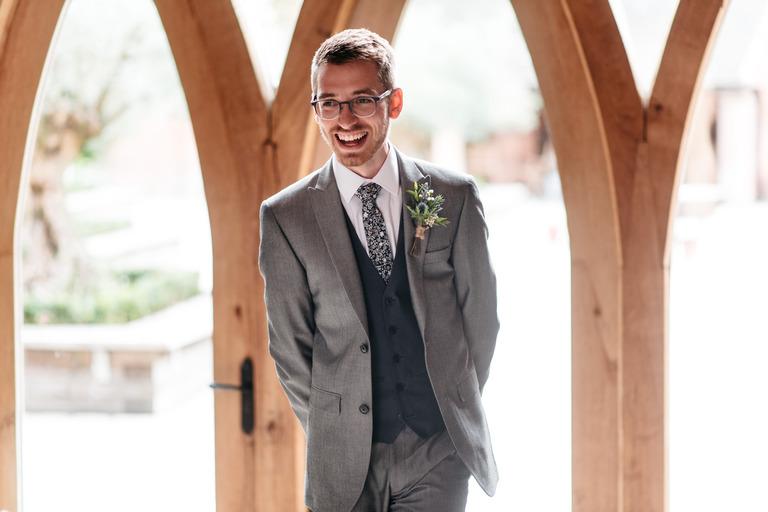 smiling, happy groom waiting at shustoke barn