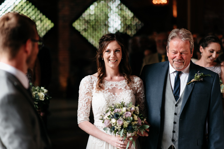smiling happy bride with her dad walking down the aisle